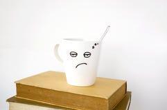 Νυσταλέο φλυτζάνι καφέ προσώπου στα βιβλία κειμένων Στοκ Φωτογραφία