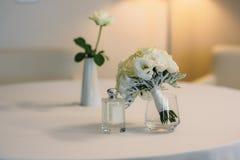 Νυφικά εξαρτήματα σε μια άσπρη καρέκλα με τα λουλούδια, ανθοδέσμη αρώματος έννοια ιματισμού Στοκ Εικόνες