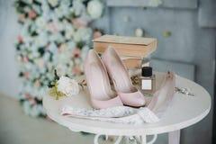 Νυφικά εξαρτήματα σε μια άσπρη καρέκλα με τα λουλούδια, παπούτσια αρώματος έννοια ιματισμού Στοκ Εικόνα