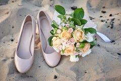 Νυφικά παπούτσια ανθοδεσμών και της νύφης στην άμμο Στοκ φωτογραφία με δικαίωμα ελεύθερης χρήσης