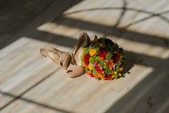 Νυφικά παπούτσια και μια ανθοδέσμη των λουλουδιών στο πάτωμα Στοκ Εικόνες
