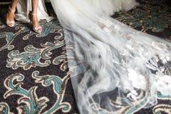Νυφικά παπούτσια κινηματογραφήσεων σε πρώτο πλάνο, πόδια, φόρεμα και πέπλο, καλύτερα εξαρτήματα για τη νύφη για την προετοιμασία  Στοκ φωτογραφίες με δικαίωμα ελεύθερης χρήσης