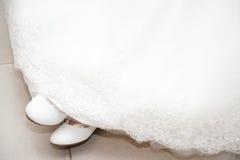 Νυφικά παπούτσια με το άσπρο φόρεμα Στοκ Εικόνα