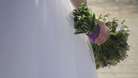 νυφικά χέρια νεόνυμφων νυφών ανθοδεσμών Η νύφη ` s Όμορφος των άσπρων λουλουδιών και της πρασινάδας απόθεμα βίντεο
