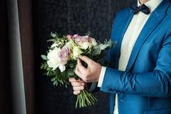 Νυφική ανθοδέσμη στα χέρια, γαμήλια ανθοδέσμη στα χέρια του νεόνυμφου, Στοκ Φωτογραφία