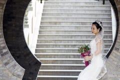 Νυφική ανθοδέσμη λαβής νυφών με το άσπρο γαμήλιο φόρεμα κοντά σε μια αψίδα τούβλου Στοκ Φωτογραφία