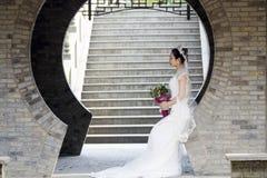 Νυφική ανθοδέσμη λαβής νυφών με το άσπρο γαμήλιο φόρεμα κοντά σε μια αψίδα τούβλου Στοκ εικόνα με δικαίωμα ελεύθερης χρήσης