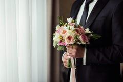 Νυφική ανθοδέσμη στα χέρια, γαμήλια ανθοδέσμη στα χέρια του νεόνυμφου, Στοκ Εικόνες
