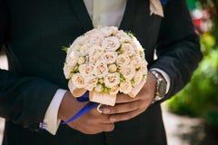 Νυφική ανθοδέσμη στα χέρια, γαμήλια ανθοδέσμη στα χέρια του νεόνυμφου, πρωί νεόνυμφων, επιχειρηματίας, γάμος, μόδα ατόμων ` s, άτ Στοκ φωτογραφία με δικαίωμα ελεύθερης χρήσης