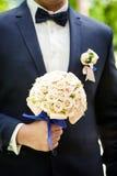 Νυφική ανθοδέσμη στα χέρια, γαμήλια ανθοδέσμη στα χέρια του νεόνυμφου, πρωί νεόνυμφων, επιχειρηματίας, γάμος, μόδα ατόμων ` s, άτ Στοκ Φωτογραφίες