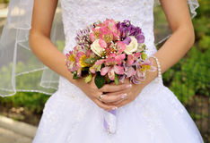 Νυφική ανθοδέσμη των πορφυρών λουλουδιών στα χέρια της νύφης Στοκ εικόνες με δικαίωμα ελεύθερης χρήσης