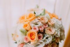 Νυφική ανθοδέσμη φιαγμένη από άσπρα, ρόδινα και πορτοκαλιά τριαντάφυλλα με δύο γαμήλια δαχτυλίδια στην κορυφή Κινηματογράφηση σε  Στοκ Φωτογραφίες