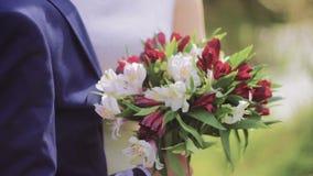 Νυφική κόκκινη & άσπρη ανθοδέσμη στα χέρια Newlywed απόθεμα βίντεο