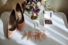 Νυφική σύνθεση λεπτομερειών πρωινού Τοπ άποψη των γαμήλιων δαχτυλιδιών, όμορφη ανθοδέσμη των ιωδών λουλουδιών με τις κορδέλλες στοκ εικόνα με δικαίωμα ελεύθερης χρήσης