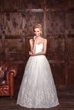 Νυφικός πυροβολισμός ομορφιάς μόδας Όμορφη νύφη μόδας στην τοποθέτηση γαμήλιων φορεμάτων μπροστά από το ξύλινο υπόβαθρο στοκ φωτογραφία
