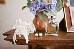 Νυφικό άρωμα, άσπρο garter και κομψά γαμήλια σκουλαρίκια ο δαντελλών Στοκ Εικόνα