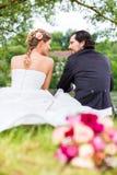 Νυφικό ζευγάρι με τη συνεδρίαση ανθοδεσμών στο λιβάδι Στοκ εικόνες με δικαίωμα ελεύθερης χρήσης