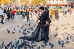 Νυφικό ζεύγος σε έναν πυροβολισμό φωτογραφιών με τα περιστέρια στη Notre Dame, ζευγάρια, Γαλλία Στοκ Φωτογραφίες