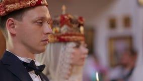 Νυφικό ζεύγος στην εκκλησία στην κινηματογράφηση σε πρώτο πλάνο ημέρας γάμου φιλμ μικρού μήκους