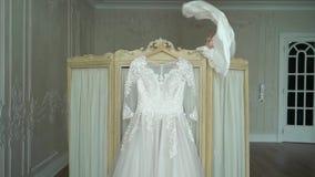 Νυφών που βάζει στο γαμήλιο φόρεμα φιλμ μικρού μήκους