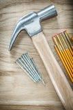 Νυχιών ανοξείδωτα καρφιά μετρητών σφυριών ξύλινα στο ξύλινο κτήριο πινάκων Στοκ φωτογραφία με δικαίωμα ελεύθερης χρήσης