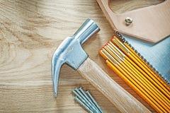Νυχιών σφυριών ξύλινα καρφιά handsaw μετρητών αιχμηρά στον ξύλινο πίνακα const Στοκ Εικόνες