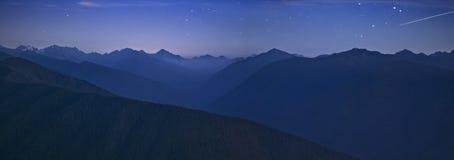 Νυχτερινός ουρανός και ολυμπιακή σειρά βουνών με το αστέρι πυροβολισμού στοκ εικόνες