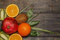 νωποί καρποί τροπικοί Ακτινίδιο, πορτοκάλι, ρόδι Σε μια ξύλινη ανασκόπηση επάνω από την όψη Στοκ Φωτογραφία