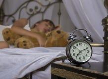 Νωρίς ξυπνώντας Ξυπνητήρι που στέκεται στον πίνακα πλευρών Ξυπνήστε ενός κοιμισμένου νέου κοριτσιού που κρατά teddy αφορτε στο κρ Στοκ Φωτογραφία
