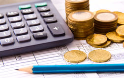 Νόμισμα, ένας υπολογιστής, ένα μολύβι στην επιχείρηση Στοκ Εικόνες