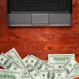 Νόμισμα και φορητός προσωπικός υπολογιστής δολαρίων χρημάτων στο ξύλινο υπόβαθρο, επιχειρησιακή έννοια, κενό διάστημα, χλεύη επάν Στοκ Εικόνες