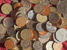 Νόμισμα λιβρών, Ηνωμένο Βασίλειο πέρα από το κόκκινο υπόβαθρο βελούδου Στοκ Φωτογραφίες