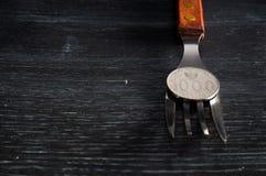 Νόμισμα στο δίκρανο στο μαύρο ξύλινο υπόβαθρο σύστασης Στοκ Φωτογραφία