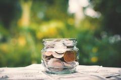 Νόμισμα στο βάζο γυαλιού στο παλαιό ξύλο Στοκ εικόνες με δικαίωμα ελεύθερης χρήσης