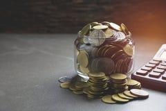 Νόμισμα σωρών με το μαύρο υπολογιστή και ένα άλλο νόμισμα Στοκ φωτογραφία με δικαίωμα ελεύθερης χρήσης