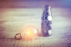 Νόμισμα της Mony στο μπουκάλι με το mony νόμισμα λαμπών φωτός πυράκτωσης στο πνεύμα μπουκαλιών Στοκ Εικόνες