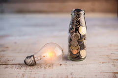 Νόμισμα χρημάτων στο μπουκάλι με το νόμισμα χρημάτων λαμπών φωτός πυράκτωσης στο πνεύμα μπουκαλιών Στοκ φωτογραφία με δικαίωμα ελεύθερης χρήσης