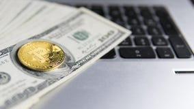 Νόμισμα Bitcoin με το lap-top και τα αμερικανικά δολάρια Χρυσά νομίσματα Bitcoin στα τραπεζογραμμάτια και το lap-top δολαρίων Cry Στοκ Εικόνες