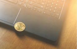 Νόμισμα Bitcoin που τοποθετείται στο σύγχρονο μαύρο πληκτρολόγιο σημειωματάριων Η φωτογραφία Bitcoin κινηματογραφήσεων σε πρώτο π Στοκ Εικόνες