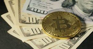 Νόμισμα Bitcoin στα τραπεζογραμμάτια δολαρίων που περιστρέφουν σε ένα μαύρο υπόβαθρο απόθεμα βίντεο
