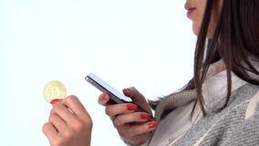 Νόμισμα Bitcoin στο χέρι και το smartphone της γυναίκας απόθεμα βίντεο