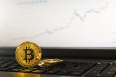 Νόμισμα cryptocurrency Bitcoin που στέκεται στο πληκτρολόγιο lap-top με το ανερχόμενος διάγραμμα στο υπόβαθρο Στοκ Εικόνες