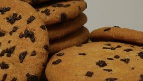 Νόστιμα μπισκότα κέικ τσιπ με τη ρηχή κινηματογράφηση σε πρώτο πλάνο κομματιών σοκολάτας απόθεμα βίντεο