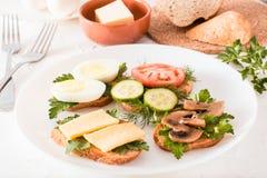 Νόστιμα σάντουιτς σε ένα πιάτο και δίκρανα σε έναν πίνακα Στοκ εικόνα με δικαίωμα ελεύθερης χρήσης