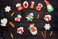 Νόστιμα σπιτικά μπισκότα μελοψωμάτων Χριστουγέννων στον ξύλινο πίνακα, τοπ άποψη Οι νέοι ψημένοι αριθμοί έτους το 2018, επίπεδοι  στοκ εικόνα