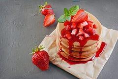 Νόστιμα σπιτικά τηγανίτες προγευμάτων και σιρόπι μούρων με τη φρέσκια φράουλα Στοκ Φωτογραφίες