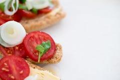 Νόστιμα τρόφιμα δάχτυλων των κρεμμυδιών άνοιξη και των ντοματών κερασιών και οργανικό τυρί με το βασιλικό στο ψημένο ψωμί brusche στοκ εικόνες