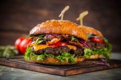 Νόστιμα burgers στον ξύλινο πίνακα Στοκ φωτογραφία με δικαίωμα ελεύθερης χρήσης