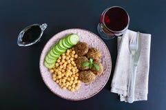 Νόστιμα cutlets κρέατος, chickpeas, φρέσκο αγγούρι σε ένα κεραμικό πιάτο και ένα ποτήρι του κρασιού σε ένα μαύρο υπόβαθρο Στοκ Εικόνες
