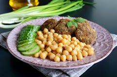 Νόστιμα cutlets κρέατος, chickpeas, φρέσκο αγγούρι σε ένα κεραμικό πιάτο σε ένα μαύρο υπόβαθρο Στοκ Εικόνες